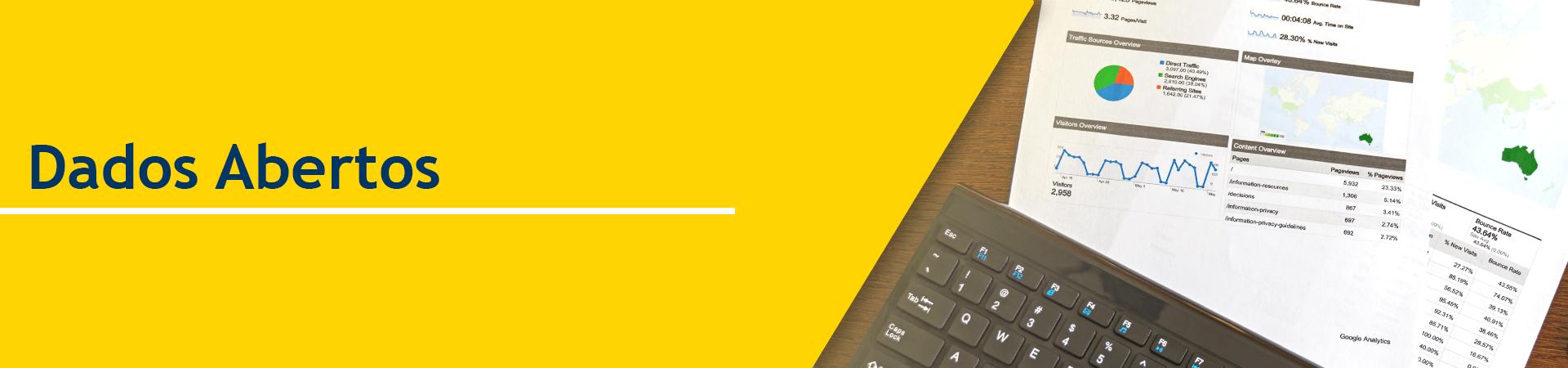 Foto de uma parte de um teclado em sua frente folhas com gráficos e informações. Frase do banner: Dados Abertos