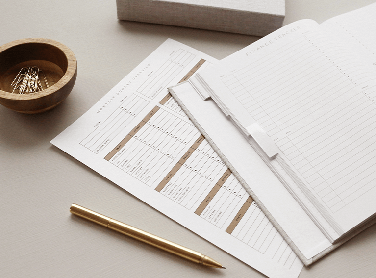 Foto de uma agenda em branco, aberta sobre a mesa. Ao lado uma caneta e acima clipes em um recipiente