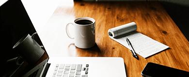 Foto de uma mesa de trabalho com notebook, bloco de notas e caneta e uma caneca com café.