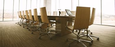 Foto de uma mesa grande, em sua volta várias cadeiras
