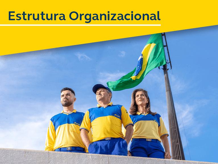 Foto de três carteiros em pé, ao fundo a bandeira do Brasil