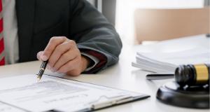 Homem com caneta a mão lê um documento. Ao seu lado um malhete