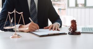 Homem assina um documento. Em seu lado direito um malhete, do lado esquerdo uma balança da justiça