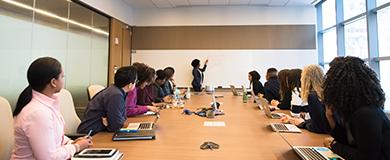 Pessoas em reunião, sentadas em volta de uma mesa, enquanto outra apresenta números e texto em um quadro branco ao fundo