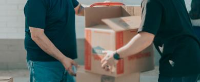 Duas pessoas carregando caixas de papelão. Ambas com camisa azul escuro e calça jeans