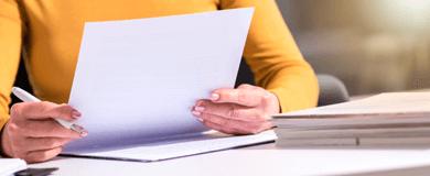 busto de uma pessoa usando camisa amarela segurando uma folha de papel à mesa.