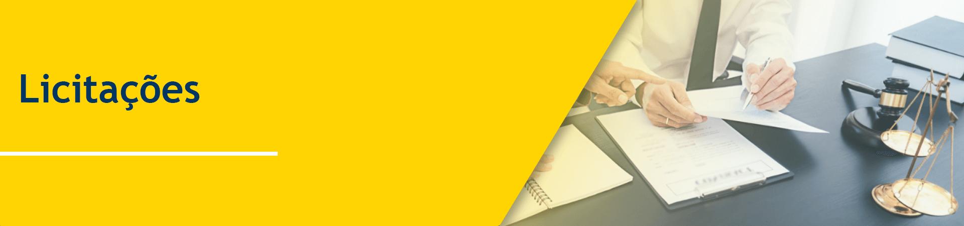 Busto de um homem usando camisa branca e gravata preta sentado à mesa segurando uma folha de papel, apontando com a caneta para uma parte da folha. Mesa preta com uma balança de pêndulo antiga, feita de metal similar a cobre. à direta da mesa dois livros pretos empilhados.