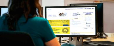 Mulher de cabelos curtos pretos vestindo camisa verde, de frente para a tela de um computador mostrando o site licitações-e do Banco do Brasil