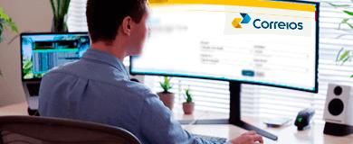 Homem vestindo camisa social azul sentado em frente à tela curva de um computador, na tela a logo dos Correios. Do lado direito uma caixa de som pequena, branca, com auto falantes pretos. À esquerda um notebook aberto com vários números na tela.