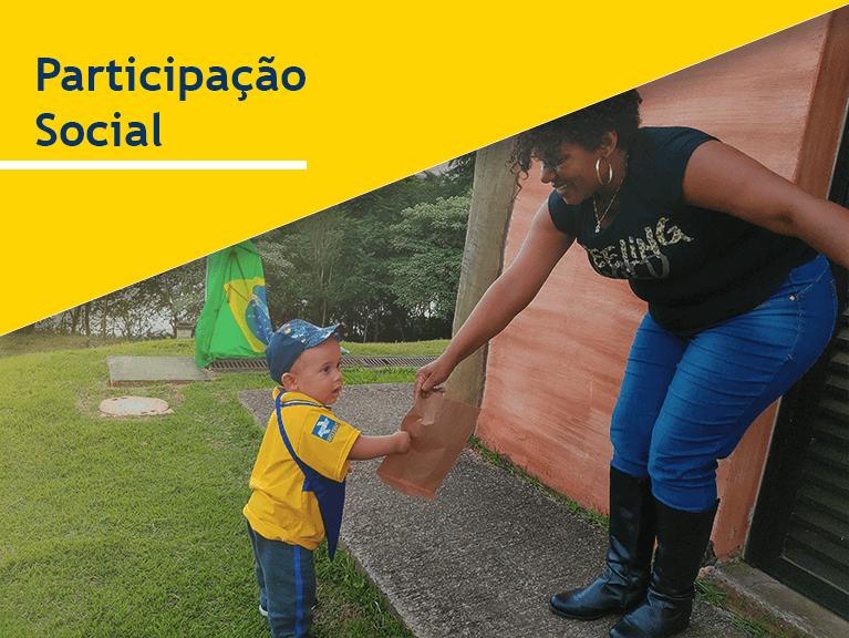 Carteiro e uma criança fantasiada com a roupa de carteiro entregam envelopes a uma mulher que segura a bandeira do Brasil. Frase do banner: Participação Social