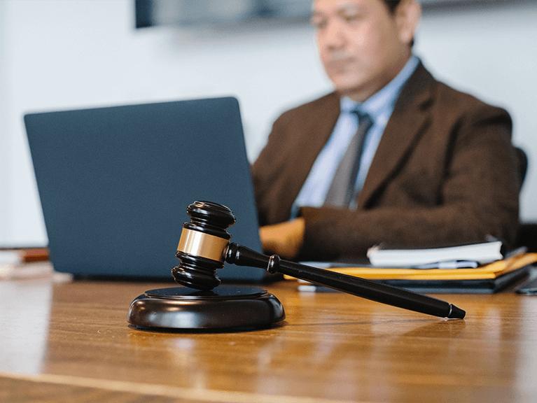 em destaque a imagem de uma martelo de juiz, ao fundo uma pessoa de terno utilizando um notebook