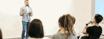 Uma pessoa a frente de uma sala realizando a explanação de conteúdo aos outros.