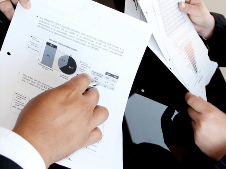 Um pessoa com relatórios impressos em uma folha de papel, mostrando um dos gráficos à outra pessoa que esta ao seu lado, segurando outro relatório impresso em uma folha de papel contendo um gráfico..