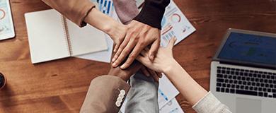 Seis pessoas em escritório com as mãos juntas e sobrepostas
