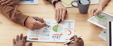 Pessoas em um escritório apontando para página com dados e gráficos