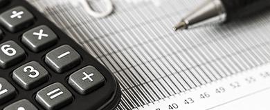 Calculadora e caneta sob uma página tabelada