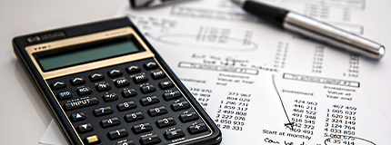 Calculadora e caneta em cima de uma página tabelada.