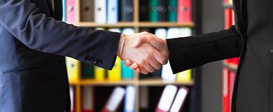 Duas pessoas apertando as mãos em um escritório.