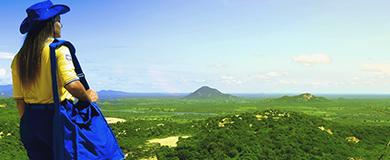 Carteira uniformizada olhando o horizonte em cima de uma montanha.