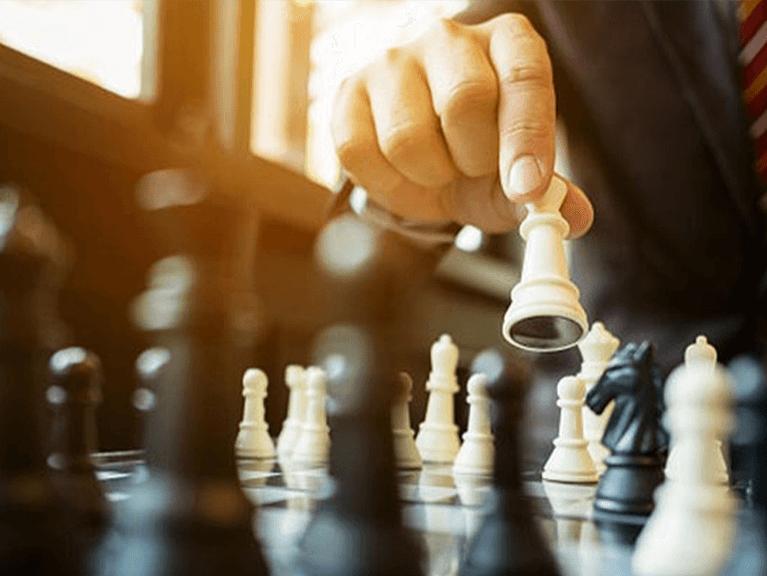 Uma mão movimentando uma peça em  uma tabuleiro de xadrez.