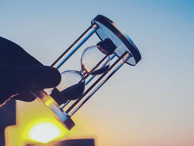 Mão com uma pequena ampulheta em mãos, com o reflexo de uma luz ao fundo.