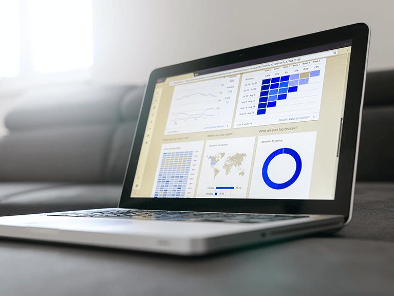 notebook aberto sobre uma superfície, com vários gráficos sendo exibidos na tela