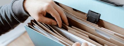 Mão procurando documento em pasta cheia de divisória.