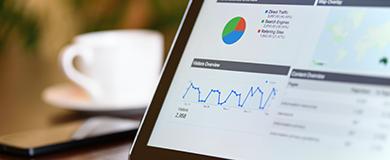 Tela com dados e gráficos estatísticos em cima de uma mesa de escritório