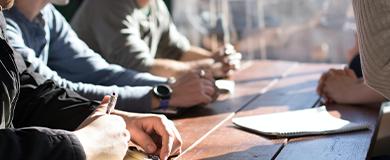 Quatro pessoas em mesa de escritório. Imagem enquadrada nas mãos das pessoas.