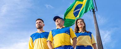 Dois carteiros e uma carteira uniformizados em frente á um mastro com bandeira do Brasil.