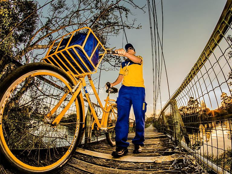Carteiro com bicicleta dos Correios passando por uma ponte localizada acima de um rio