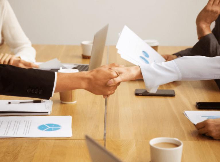 duas pessoa apertando as mãos, em um mesa de reunão com outros membros