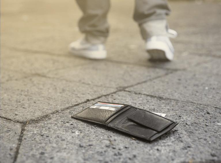 Carteira caida no chão. Pedestre ao fundo indo embora