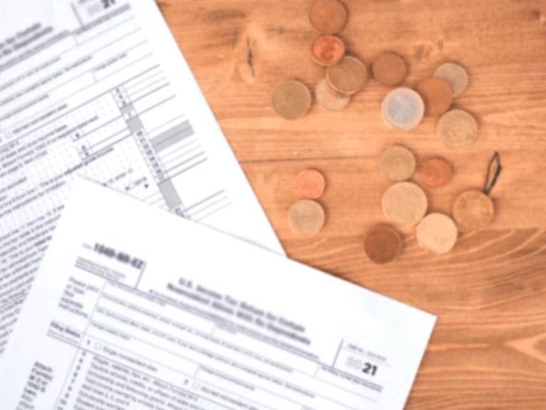 papeis de cobrança de impostos e moedas em cima de uma superfície