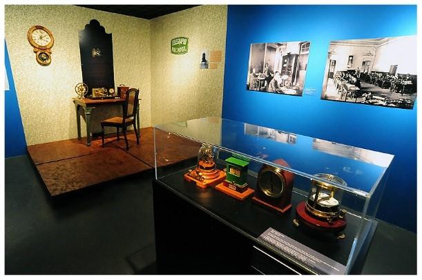 Exposição Os Sinais e as Coisas. Escrivaninha antiga com relógio na parede. Estandarte com quatro relógios antigos.