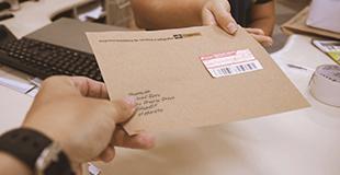 mão segurando envelope pardo com etiqueta de carta registrada