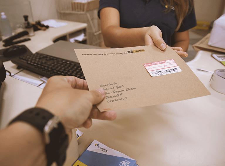 Envelope pardo com etiqueta de carta registrada sendo postada em agência dos Correios