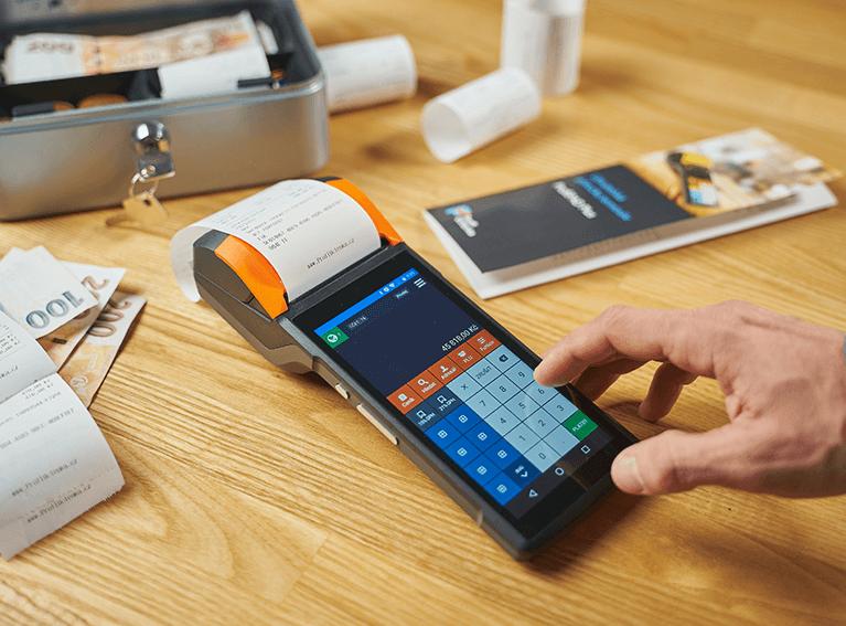 Sob a mesa uma caixa aberta com notas de dinheiro, papéis e uma máquina de cartão de crédito com uma mão digitando um número.
