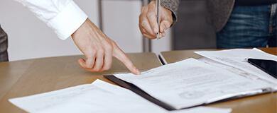 Papeis em cima de uma mesa sendo assinados