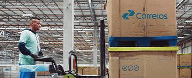 Homem em empilhadeira, levando duas caixas com encomendas