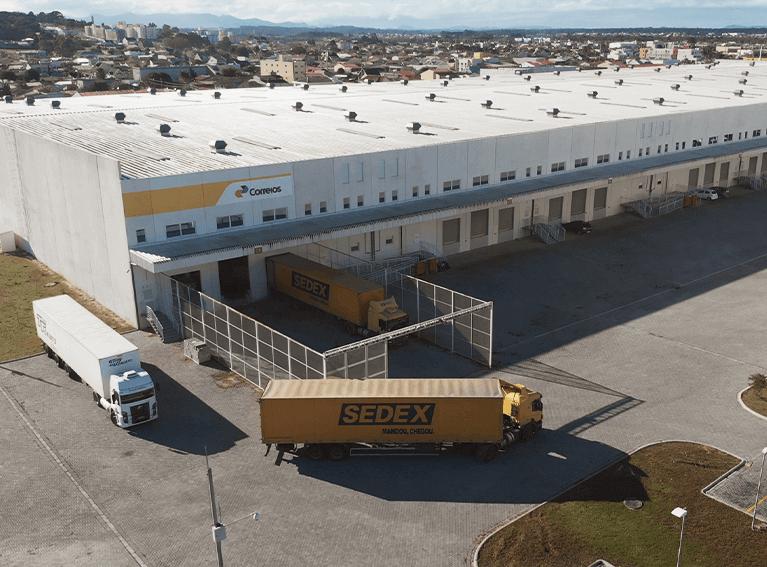 Frente de um centro logístico em visão aérea. Três carretas dos Correios saindo para distribuição.