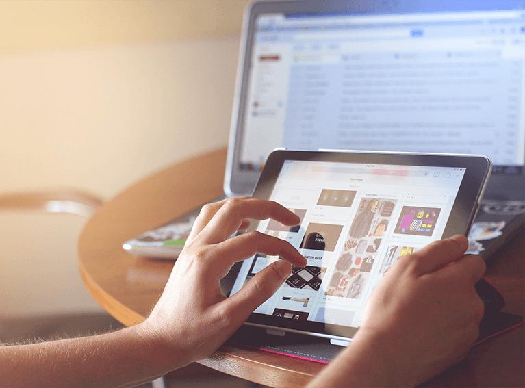 Pessoa pesquisando em site de vendas através de um tablet. Ao fundo, um monitor de computador em outro site de e-commerce.