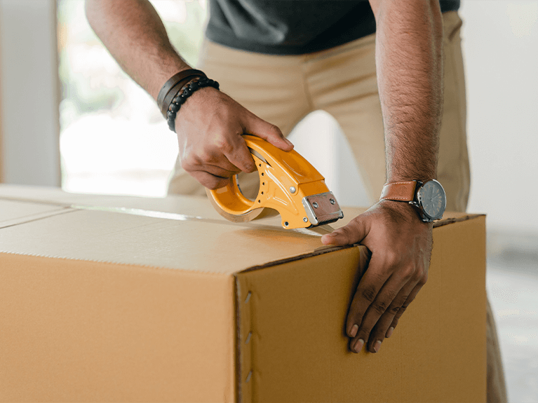 Homem lacrando parte superior de uma caixa de papelão com fita transparente