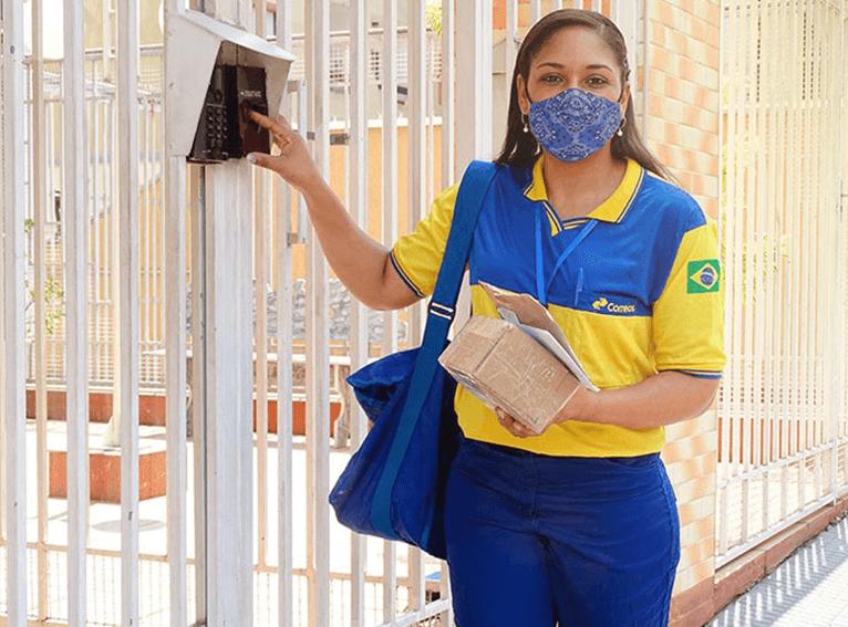 uma carteira uniformizada, tocando o interfone de uma residência para a entrega de uma encomenda